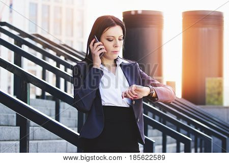 Time Is Money. Portrait Of Confident Business Woman In Formal Wear Watching On Her Watches While Tal
