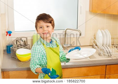 Portrait of six years old boy in rubber gloves holding plate and sponge scourer during dishwashing
