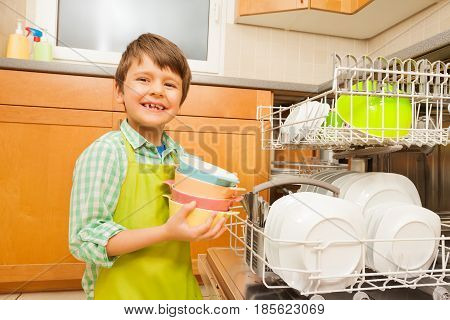 Portrait of smiling kid boy in apron pulling out colorful ceramic bowls of the dishwasher