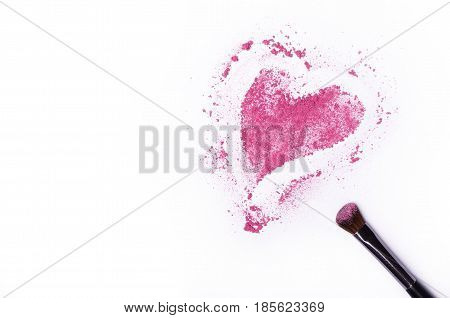 Heart shaped crushed eye shadows with brush isolated on white background. Pink shadows on white table free space.
