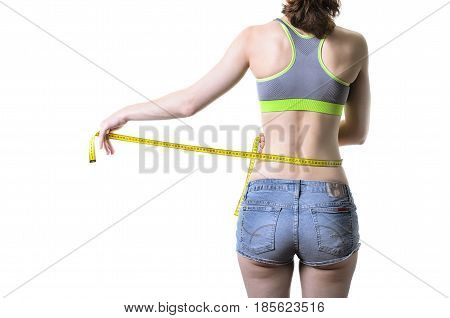 Slender Young Woman Measures Herself With A Measuring Tape, Isolated On White.