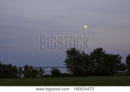 Landscape view of the early evening moon over water with trees and foliage in the left foreground near Cornwall, Ontario in early August.