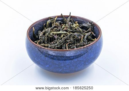 Chinese Oolong Green tea . (Feng Huang Dan Cong) in a blue ceramic bowl isolated on white.