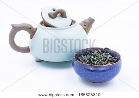 Chinese Green tea. (Huang Shan Mao Feng) in a blue ceramic bowl with small clay pot isolated on white.