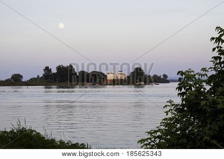 Cornwall, Ontario - August 9, 2014 -- Close up of the early evening moon over water with a cargo ship going through a canal edged by trees and foliage near Cornwall Ontario in early August.