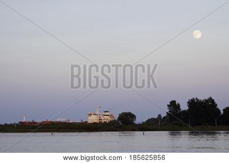 Cornwall Ontario - August 9 2014 -- Close up of the early evening moon over water with a cargo ship going through a canal edged by trees and foliage near Cornwall Ontario in early August.