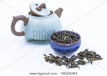 Chinese Oolong Green tea. (Feng Huang Dan Cong) in a blue ceramic bowl with small clay pot isolated on white.