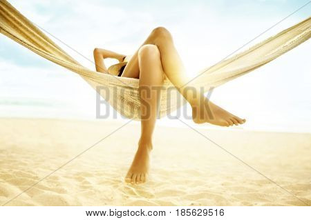 Woman relaxing in hammock with bare feet on beach