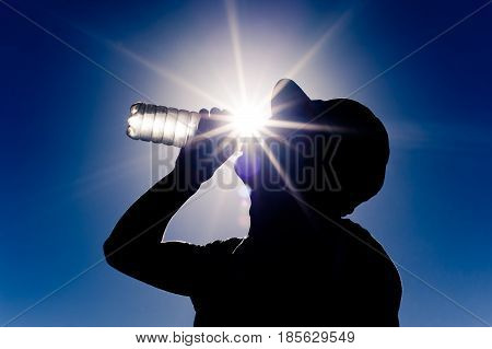 man drinking water under the heat of the sun. Thirsty man drinking.