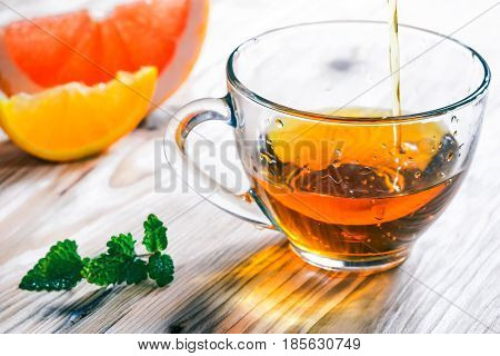 Pouring tea into glass cup. Fresh orange and grapefruit and mint leaves on the raw wood table. Close up view