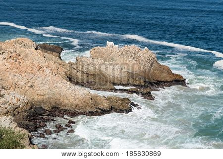 A rocky outcrop resembling a dragon in the sea next to Clarence Drive between Gordons Bay and Rooi-Els