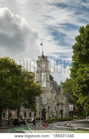 Auckland New Zealand - March 4 2017: The gray stone clock tower and building of public Auckland Art Gallery set along the street with green vegetation. Blue sky with white clouds and traffic scenery.