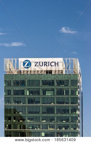 Auckland New Zealand - March 4 2017: Green glass office building of Zurich Insurance isolated against blue sky. Large logo and name on top captured in white metal frame.