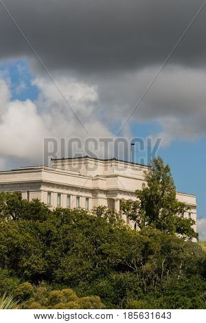 Auckland New Zealand - March 4 2017: War Memorial Museum building behind green vegetation and under rainy cloudy sky as seen from Parnell road.