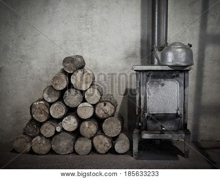 Firewood next to an old woodburner in a hut