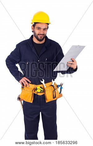 Handsome beard young worker smiling and holding a clipboard guy wearing workwear and yellow helmet with belt equipment isolated on white background