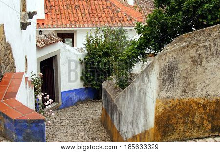 Obidos, Portugal. Beautiful tiny cobblestoned street, walls, and roofs on different levels. Obidos is an ancient medieval Portuguese village originated in the 11th century and still situated within the same castle walls.