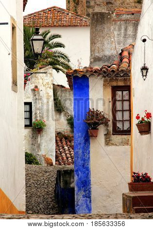 Obidos, Portugal. Beautiful tiny yards, walls, and roofs on different levels. Obidos is an ancient medieval Portuguese village originated in the 11th century and still situated within the same castle walls.