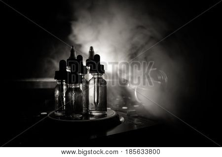 Vape And Dj Club Concept. Smoke Clouds And Vape Liquid Bottles On Dj Mixer Close Up. Light Effects.