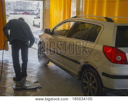 The worker thoroughly washes the silver car