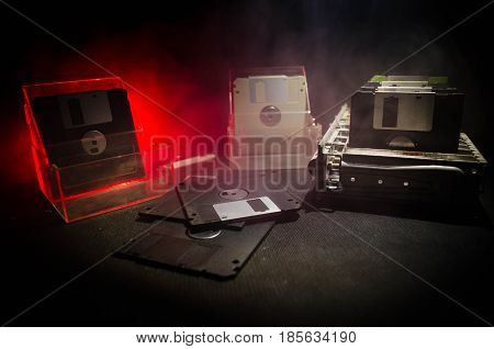 Pile of black floppy disks (diskette) on dark background with light
