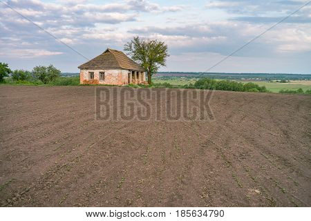 old abandoned house in rural landscape with soil field