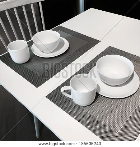 Simple table setting in white and gray tones.