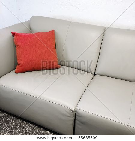 Red cushion decorating a simple gray leather sofa.