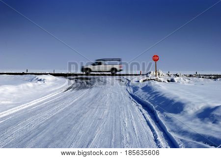 Stop sign at intersection in Winter on a snowy road