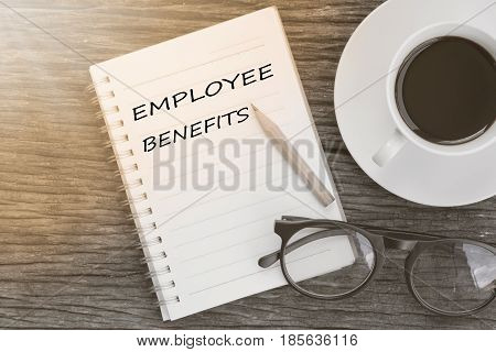 Concept employee benefits message on notebook with glasses pencil and coffee cup on wooden table.