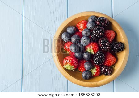 Mixed Berry Fruits In Wooden Bowl On Light Blue Wood Planked Table From Above