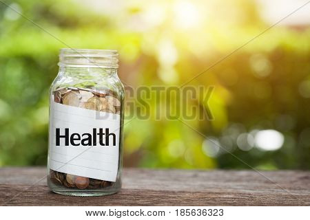Health word with coin in glass jar concept siphons money and Health insurance.