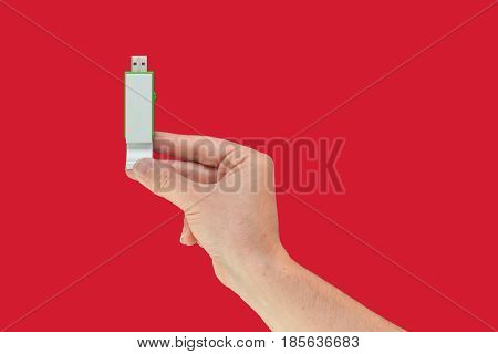 Green USB flash on hand with isolated red background