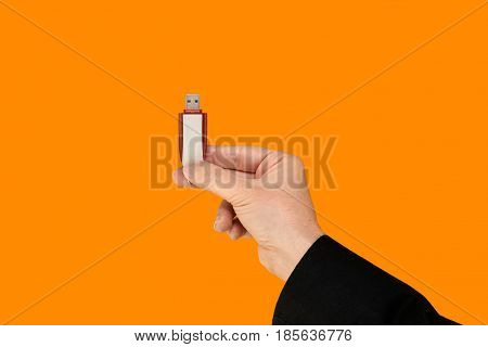 Red flash memory on hand with isolated orange background