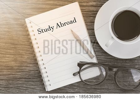Concept Study Abroad message on notebook with glasses pencil and coffee cup on wooden table.