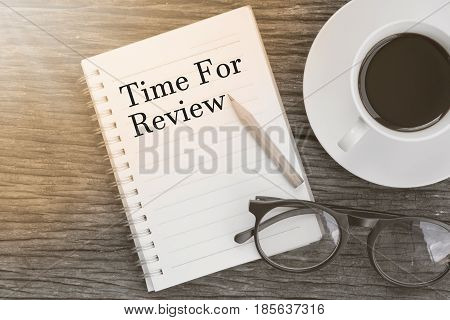 Concept Time For Review message on notebook with glasses pencil and coffee cup on wooden table.