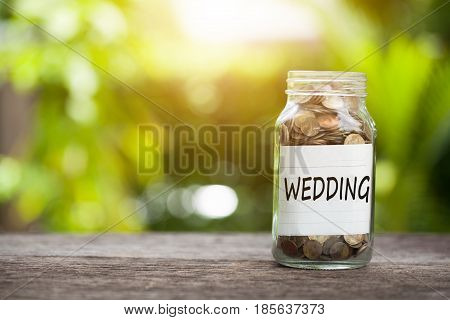 WEDDING word with coin in glass jar Savings for budget concept.