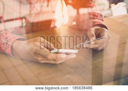 Young woman holding a credit card to purchase online shopping.Hipster man to use credit card with smart-phone for shopping.Girl is shopping online.Shopping online is very easy.Vintage filter.