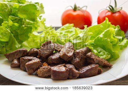 Fried Beef Goulash With Lettuce Leaves On A White Plate And Tomatoes In The Background. Tasty And Nu