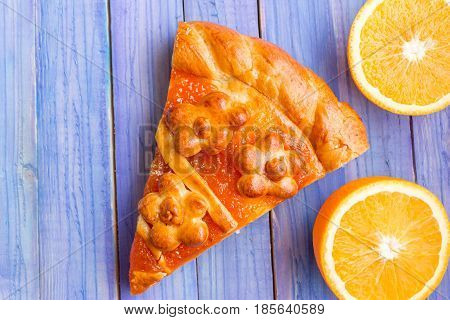A piece of cake with orange confiture on a wooden table. Delicious dessert.