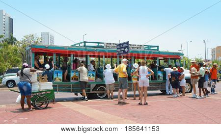Cartagena de Indias, Bolivar / Colombia - April 10 2016: Tourists boarding a Chiva for tour through the historic center of Cartagena. Cartagena's colonial walled city is a UNESCO World Heritage Site