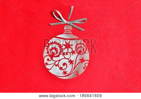 Christmas ball decoration on red glittering background. Silver ribbon on top.