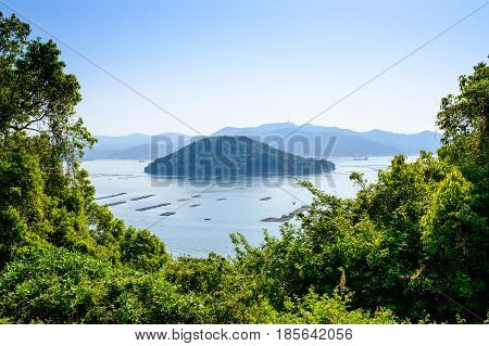 Inland sea near Hiroshima with vegetation and oyster racks