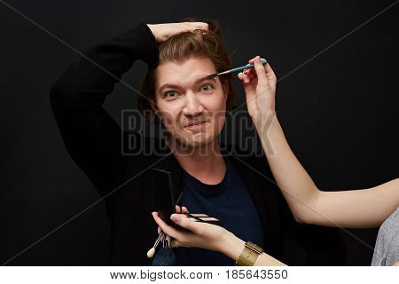 Professional Make-up artist doing man makeup in studio. Make-up process. Model and make-up artist have fun.