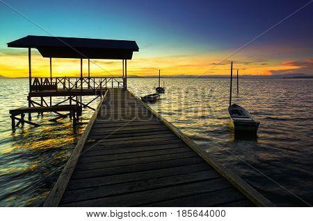 Wooden bridge of fisherman jetty & fishing boat with beautiful sunrise in Tanjung Aru village,Labuan Pearl of Borneo,Malaysia.