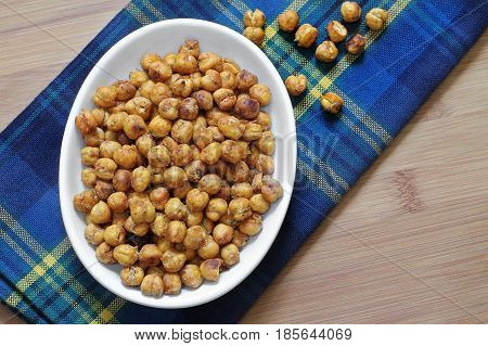 A healthy snack of roasted chick peas garbanzo beans. Top view macro with copy space.