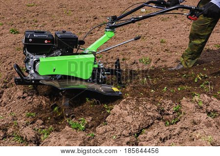 Farmer is working with green cultivator machine.