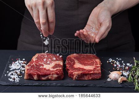 A Female Chef Sprinkles Sea Salt With Two Fresh Raw Ribeye Steaks From Marbled Beef On A Dark Backgr