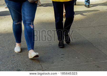 womens legs walking on a pedestrian crossing on a sunny day
