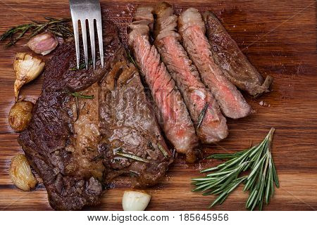 Grilled Rib-eye Steak Of Marble Beef Closeup With Spices On A Wooden Board. Juicy Steak Medium Rare,